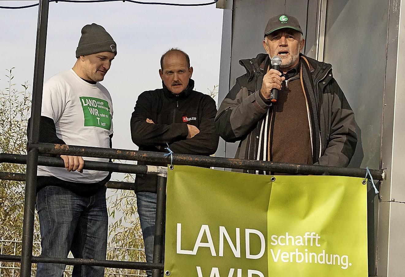 """Thomas Frenk (links), Beiratsmitglied  von """"Land schafft Verbindung"""", bat BLHV-Präsident Werner Räpple (rechts) und Stefan Lehmann, Mitglied im Bundesvorstand des Bundesverbandes Deutscher Milchviehhalter (BDM), gemeinsam auf die Kundgebungsbühne."""